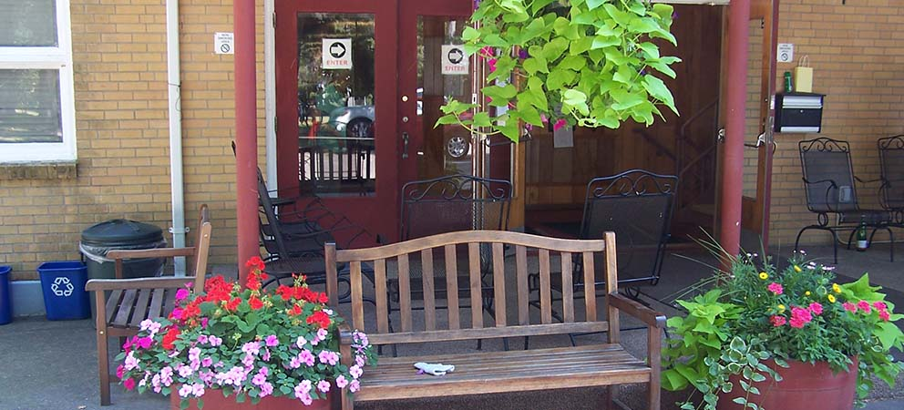 : A bench with pink and red potted plants and a green leafy plant hanging from porch with doors beyond