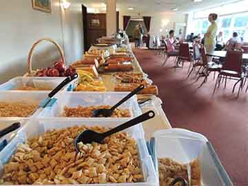 An assortment of cereals on a long table with more food in a dining room with people sitting at tables